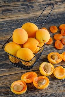 Abricots aux abricots secs dans une passoire sur table en bois, vue du dessus.