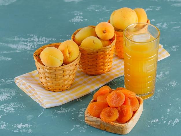 Abricots aux abricots secs, jus dans des paniers sur plâtre et toile de pique-nique, vue de dessus.