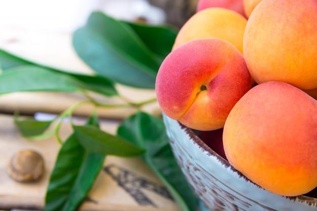 Abricots biologiques entiers mûrs dans un bol en céramique sur une boîte à fruits en bois
