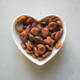Abricots biologiques séchés en assiette en forme de cœur