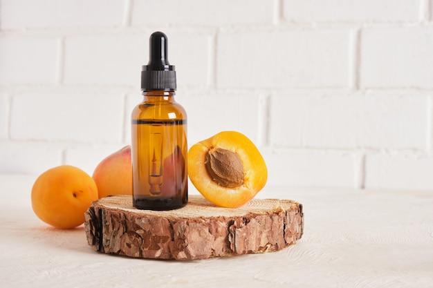 Abricots et bouteille brune en verre avec compte-gouttes pour cosmétiques sur fond de mur de briques blanches