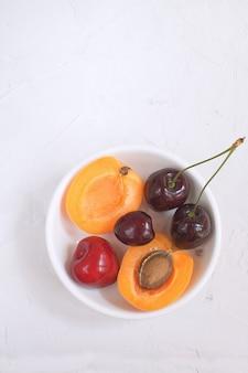 Abricots et cerises dans un bol en porcelaine blanche fruits et baies d'été récolte de fruits biologiques