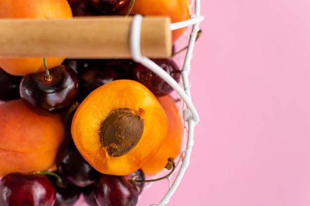 Abricots et cerises dans un panier en métal blanc