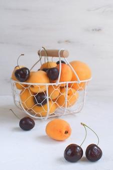 Abricots et cerises dans un panier en métal fruits et baies d'été récolte de fruits biologiques blanc