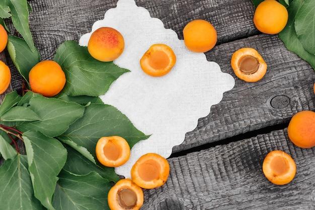 Abricots collectés rouges, mûres et fraîches avec des feuilles sur un fond de surface de table en bois ancien rustique avec espace de copie. vue d'en-haut. espace pour le texte