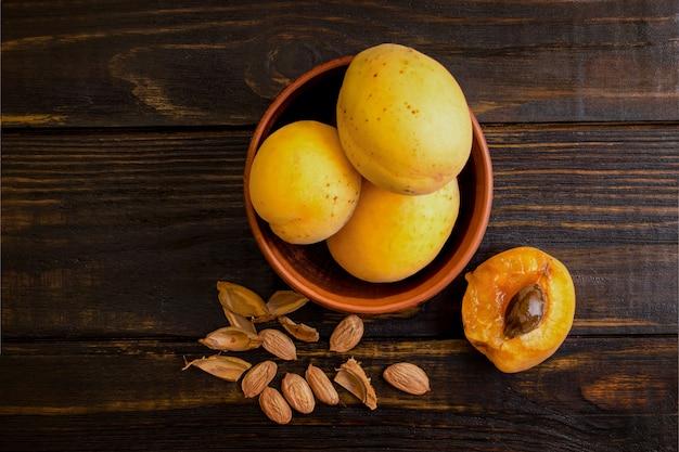 Abricots dans une assiette d'argile sur une table en bois avec des os brisés. vue de dessus