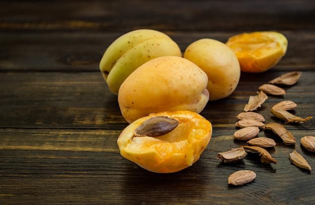Abricots dans une assiette d'argile sur une table en bois avec des os brisés.