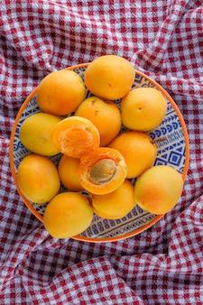Abricots dans une assiette sur une toile de pique-nique, à plat.