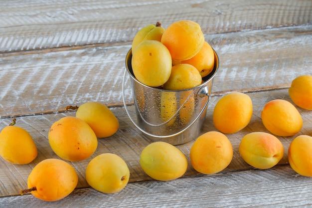 Abricots dans un mini seau sur table en bois, vue du dessus.