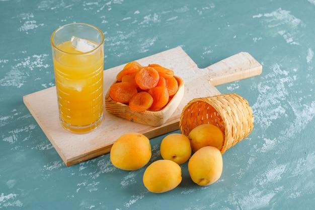 Abricots dans un panier avec abricots secs, vue de dessus de jus sur plâtre et planche à découper