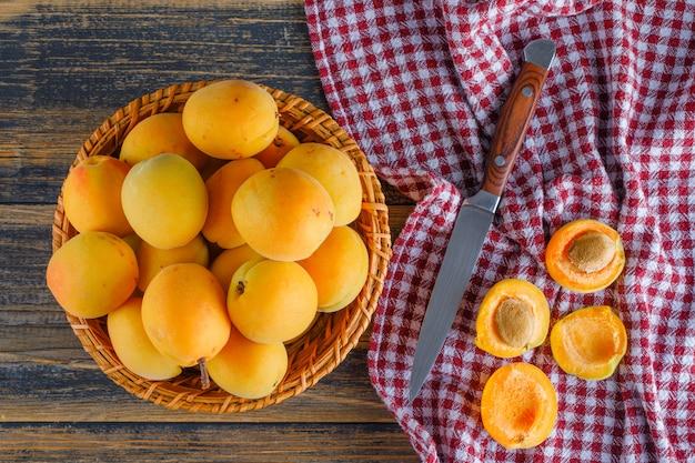 Abricots dans un panier en osier avec un couteau à plat sur un tissu de pique-nique et une table en bois