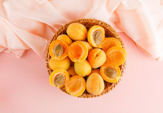 Abricots dans un panier en osier. pose à plat.