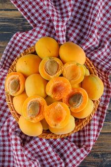 Abricots dans un panier en osier sur tissu en bois et pique-nique. pose à plat.