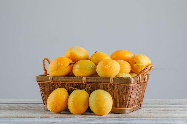 Abricots dans un panier sur table en bois. vue de côté.