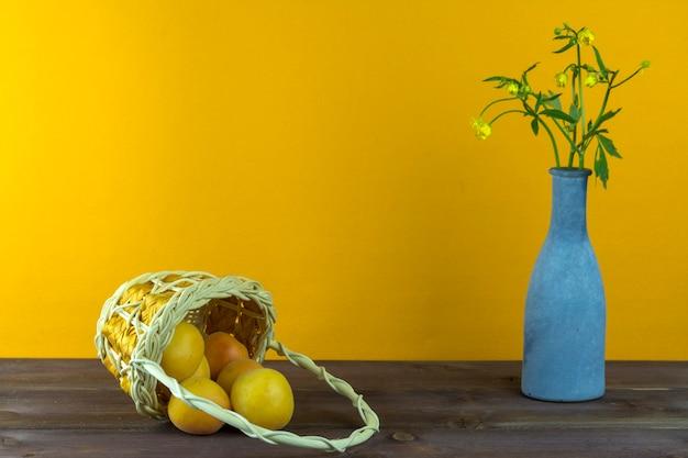 Abricots dans le panier. vase avec des fleurs sauvages sur fond jaune. ambiance d'été