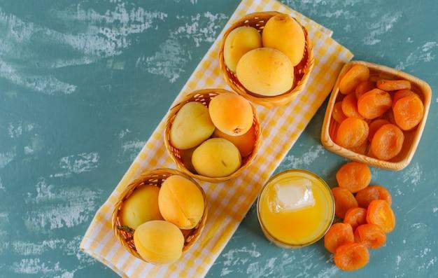Abricots dans des paniers avec des abricots secs, jus plat posé sur du plâtre et une toile de pique-nique