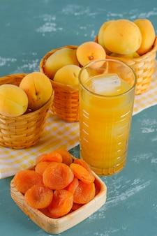 Abricots dans des paniers avec abricots secs, vue de dessus de jus sur plâtre et tissu de pique-nique