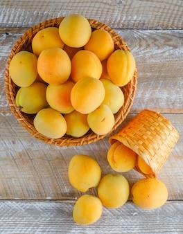 Abricots dans des paniers en osier sur une table en bois. vue de dessus.
