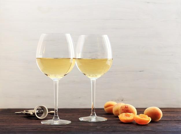 Abricots et deux verres de vin blanc