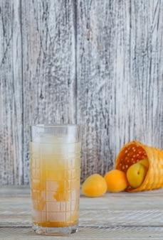 Abricots épars à partir d'un panier en osier avec vue latérale de jus sur une table en bois
