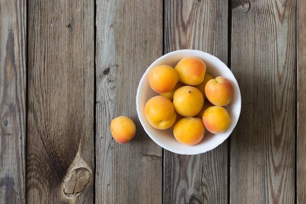 Abricots frais dans un bol sur une table en bois. espace copie