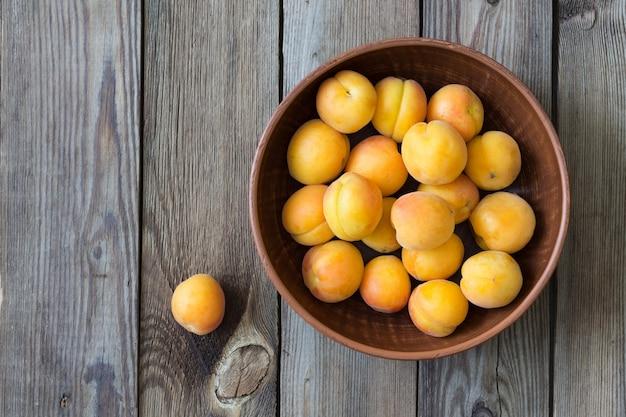 Abricots frais dans un bol sur une table en bois. style rustique