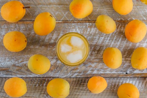 Abricots frais avec du jus de glace à plat sur une table en bois