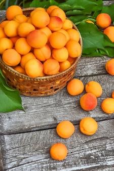Abricots frais avec des feuilles closeup isolé sur fond en bois.