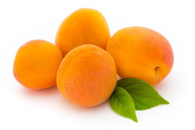 Abricots frais avec gros plan de feuilles isolé sur fond blanc.