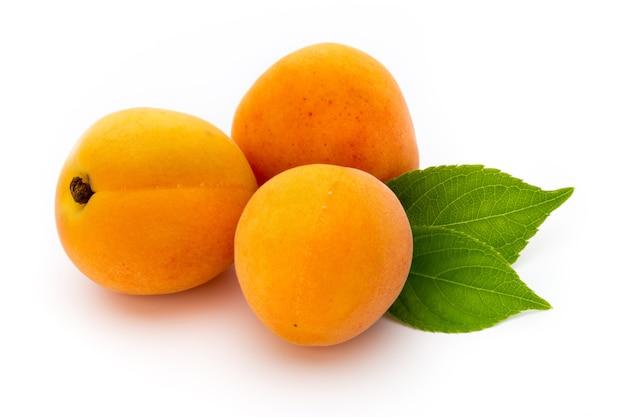 Abricots frais avec gros plan de feuilles isolé sur une surface blanche.