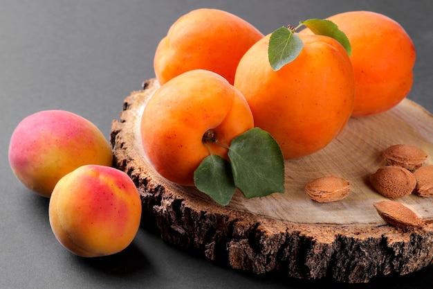 Abricots frais et mûrs sur un support en bois sur fond noir