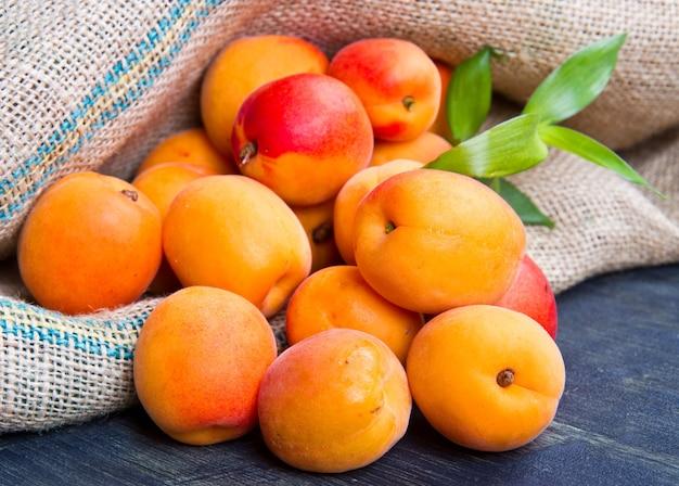 Abricots frais sur sac de jute sur bois