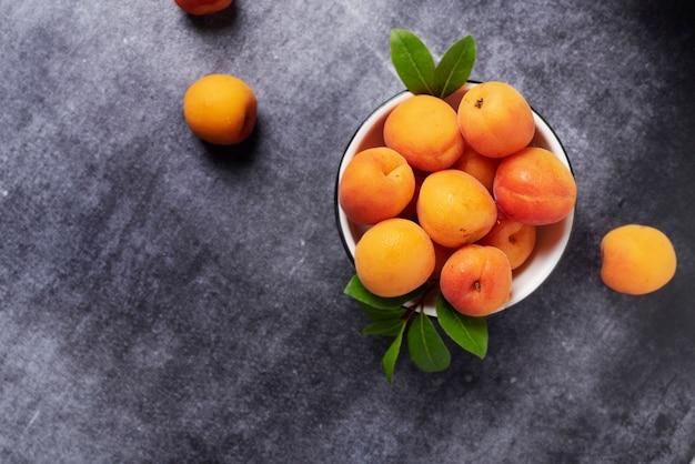 Abricots frais sucrés dans le bol blanc