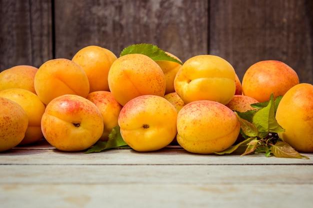 Abricots juteux mûrs jaunes sur fond en bois. mise au point sélective.