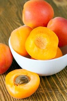 Abricots lavés frais se trouvant dans un bol blanc et certains coupés en deux