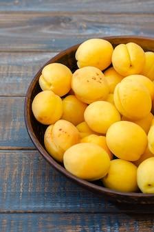 Abricots mûrs dans un bol en argile sur un fond en bois sombre.