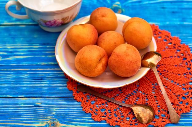 Abricots orange frais sur une assiette sur un fond en bois bleu.