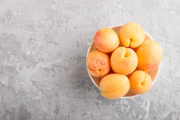 Abricots orange frais dans un bol blanc. vue de dessus.
