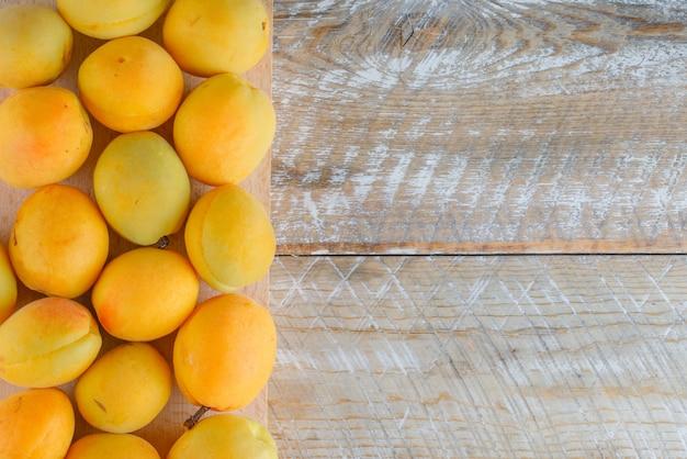 Abricots sur planche de bois et à découper, pose à plat.