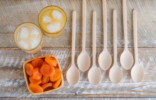 Abricots secs dans une assiette en bois avec du jus, cuillères en bois à plat sur une table en bois