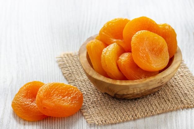 Abricots secs dans un bol sur bois clair