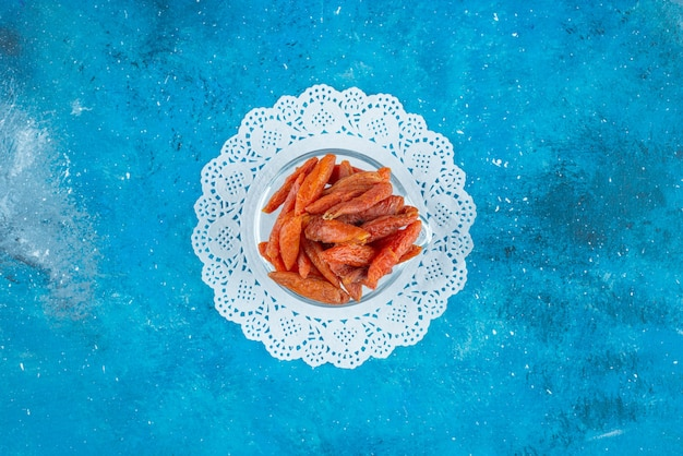 Abricots secs dans un bol sur caboteur , sur la table bleue.