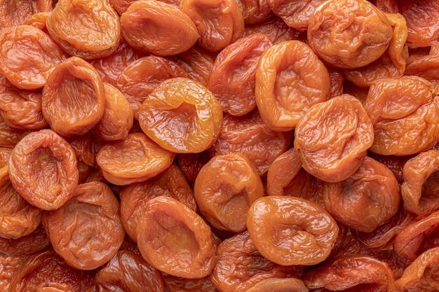 Abricots secs, fond de texture orange foncé. veganisme, végétarisme et alimentation saine. vitamines