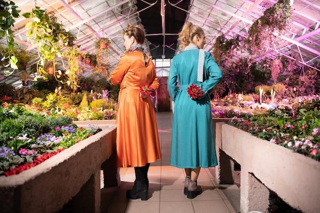 Absolument magnifique. belles femmes attirantes tenant des fleurs derrière leur dos