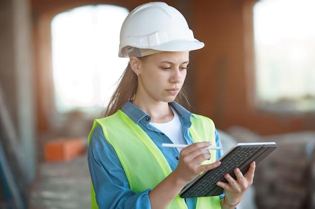Absorbé par le travail d'une femme ingénieur travaillant avec une tablette sur le chantier. portrait d'un jeune architecte, équipement de protection. mise au point sélective.