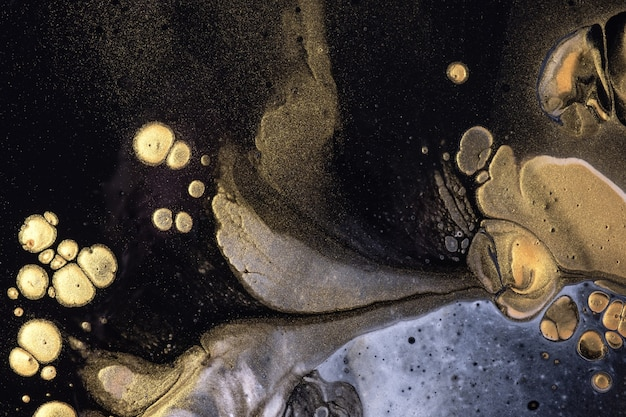 Abstrait art fluide fond noir et couleurs dorées. peinture acrylique liquide sur toile avec dégradé. toile de fond aquarelle avec motif.