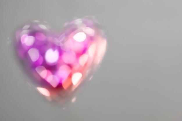 Abstrait : coeur de cristal brillant avec effet bokeh sur fond gris. bokeh en forme de coeur