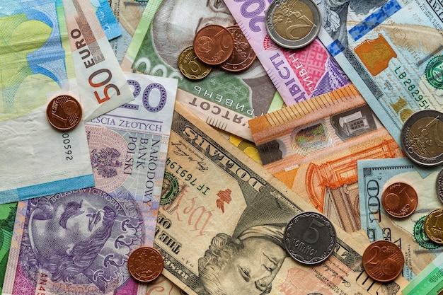 Abstrait coloré composé de différentes pièces métalliques, de billets américains, ukrainiens et de billets en euros. argent et finances, concept d'investissement réussi.