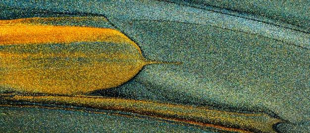 Abstrait doré. coups de peinture dorée sur fond vert. frottis scintillant d'or sur fond vert foncé