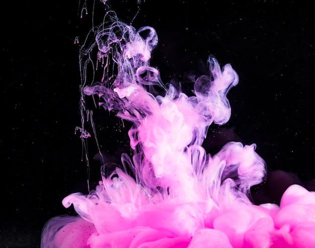 Abstrait épais brouillard rose dans un liquide sombre